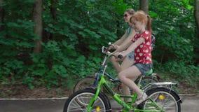Moeder en dochter die een fiets berijden stock videobeelden
