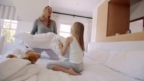 Moeder en dochter die een grappige hoofdkussenstrijd hebben stock footage