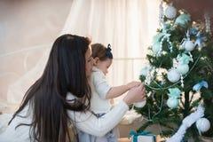Moeder en dochter die een Kerstboomspeelgoed, vakantie, gift, decor, nieuw jaar, Kerstmis, levensstijl verfraaien Stock Foto