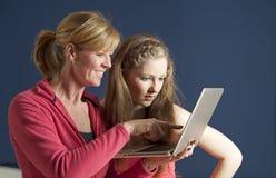 Moeder en dochter die een laptop computer met behulp van stock foto