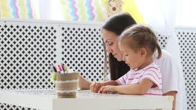 Moeder en dochter die een raadsel samen in de lichte woonkamer doen stock video