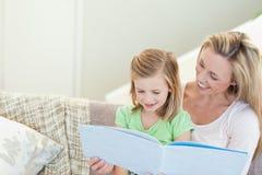 Moeder en dochter die een tijdschrift lezen stock afbeelding