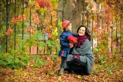 Moeder en dochter die en in de herfst lachen voor de gek houden rond Stock Foto's