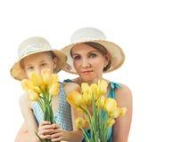 Moeder en dochter die gele die tulpen in handen houden op witte achtergrond worden geïsoleerd royalty-vrije stock afbeelding