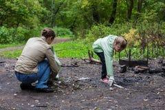 Moeder en dochter die het bos helpen schoonmaken stock foto's