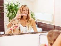 Moeder en dochter die hun tanden borstelen stock afbeelding