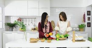 Moeder en dochter die in keuken werken stock video