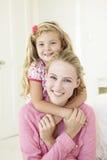 Moeder en Dochter die Knuffel hebben samen thuis stock foto's
