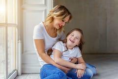 Moeder en dochter die koesteren dichtbij windiow royalty-vrije stock foto