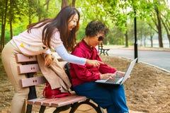 Moeder en dochter die laptop met behulp van bij tuin De dochter onderwijst een bejaarde moeder om een computer te gebruiken stock afbeelding