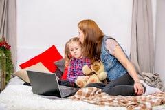 Moeder en dochter die laptop op bed in slaapkamer met behulp van Moeder koesterende en kussende dochter royalty-vrije stock afbeeldingen