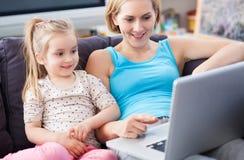 Moeder en dochter die laptop thuis met behulp van Stock Foto's
