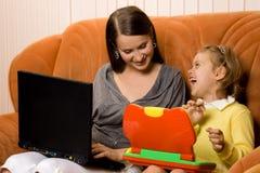 Moeder en dochter die laptops met behulp van royalty-vrije stock foto's