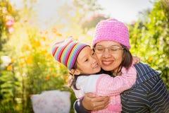 Moeder en dochter die liefde in tuin voelen Stock Afbeelding