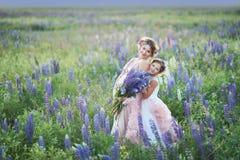 Moeder en dochter die lupinebloemen op mooi gebied op zonsondergang verzamelen Mooi meisje die in violette kleding een lupine hou stock foto
