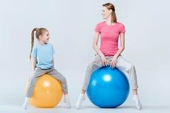Moeder en dochter die met geschiktheidsballen uitoefenen stock fotografie