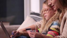 Moeder en dochter die online samen winkelen stock footage