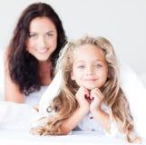 Moeder en dochter die op bed bij camera glimlachen Royalty-vrije Stock Fotografie