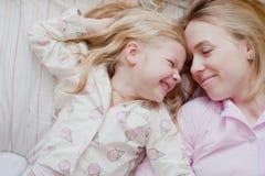 Moeder en dochter die op bed in roze pyjama's liggen Royalty-vrije Stock Afbeeldingen