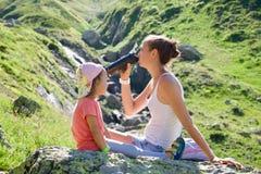 Moeder en dochter die op de grote steen bij reisexcursie rusten Stock Afbeeldingen