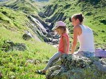 Moeder en dochter die op de grote steen bij reisexcursie rusten Stock Foto's