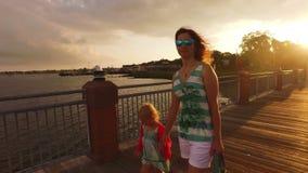 Moeder en dochter die op de pijler bij zonsondergang lopen stock footage