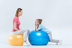 Moeder en dochter die op geschiktheidsballen rusten na opleiding royalty-vrije stock afbeeldingen