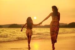 Moeder en dochter die op het strand lopen stock foto's