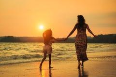 Moeder en dochter die op het strand met zonsondergang lopen royalty-vrije stock foto's