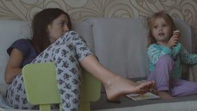 Moeder en dochter die op TV letten stock videobeelden