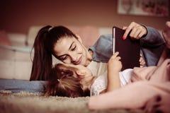 Moeder en dochter die op vloer liggen en digitale tablet gebruiken royalty-vrije stock afbeeldingen