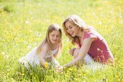 Moeder en dochter die in openlucht bloem houden Royalty-vrije Stock Foto