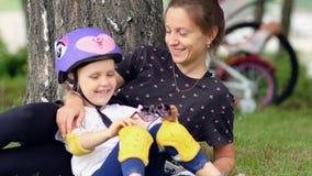 Moeder en dochter die in park na fietsrit rusten stock videobeelden