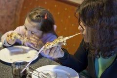 Moeder en dochter die pizza in restaurant eten royalty-vrije stock foto's