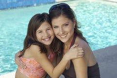 Moeder en Dochter die in Poolside omhelzen royalty-vrije stock fotografie