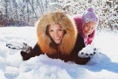 Moeder en dochter die pret in de sneeuw hebben Stock Foto