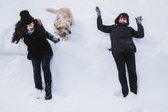 Moeder en dochter die pret met hun Golden retriever in de sneeuw hebben stock foto's