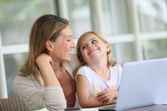 Moeder en dochter die pret op laptop hebben Stock Fotografie