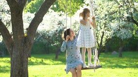 Moeder en dochter die pret op schommeling hebben samen Mooie bloeiende bomen stock video