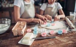 Moeder en dochter die ruw deeg met koekjessnijders snijden royalty-vrije stock fotografie