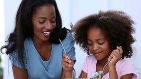 Moeder en dochter die salade mengen stock videobeelden