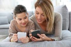 Moeder en dochter die smartphones gebruiken stock afbeeldingen
