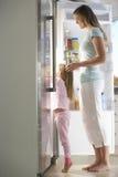 Moeder en Dochter die Snack kiezen van Koelkast royalty-vrije stock afbeelding