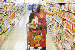 Moeder en dochter die in supermarkt winkelen stock foto's