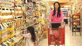 Moeder en dochter die in supermarkt winkelen stock video