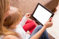 Moeder en dochter die tablet bekijken royalty-vrije stock afbeelding