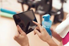 Moeder en dochter die tablet gebruiken bij de gymnastiek Zij kijken gelukkig, modieus en geschikt royalty-vrije stock foto's