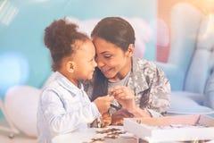 Moeder en dochter die terwijl het doen van een raadsel plakken stock fotografie