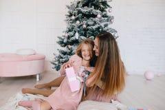 Moeder en dochter die thuis dichtbij Kerstboom koesteren vrouw en meisje met aanwezige Kerstmis Stock Foto