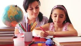 Moeder en dochter die thuiswerk op digitale tablet doen stock videobeelden